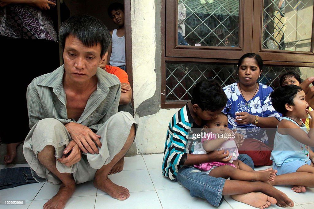 A Myanmar Buddhist (L), who escaped from beatings by Myanmar Muslims, sits with a Rohingya family (R) at a different location within a detention centre of the Medan City Immigration Offices in North Sumatra province on April 5, 2013 where a group of Myanmar Muslims earlier beat eight Myanmar Buddhists to death after they heard about communal violence in their homeland. The Rohingya Muslims launched the attack at the immigration centre on Sumatra island using weapons fashioned from smashed up beds and broom handles after seeing pictures of religious violence in Myanmar last month that left dozens dead.