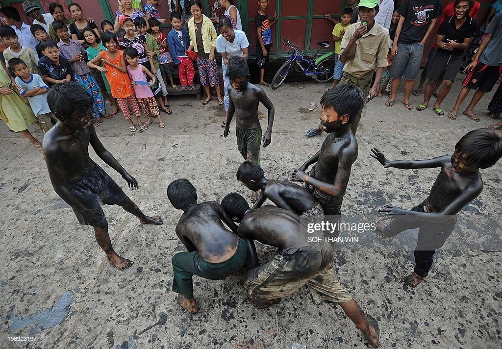 Myanmar children smeared with used car oil play a ball game with a coconut as they celebrate the 65th anniversary of Myanmar's independence, in Yangon on January 4, 2013. Myanmar, formerly known as Burma, gained independence from Britain on January 4, 1948. AFP PHOTO / YE AUNG THU