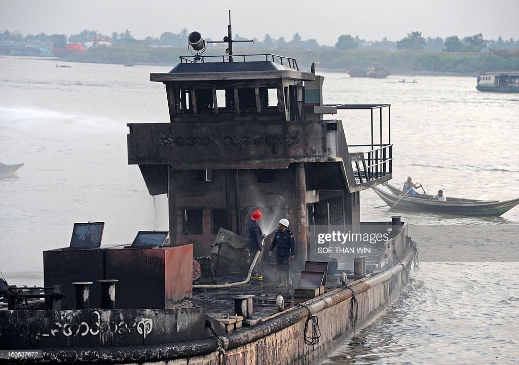 Myanmar fireman extinguish a fire on an oil-tanker that caught fire when two other oil takers caught fire and sank on Hlaing river in Yangon on February 4, 2013. At least four people were killed when two oil tankers caught fire and sank in the river in Yangon, an official said. AFP PHOTO/ Soe Than WIN