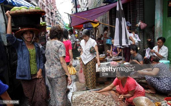A Myanmar fruits vendor makes her way through a street market in Lanmadaw township downtown Yangon on June 15 2010 Myanmar faces a tough task to...