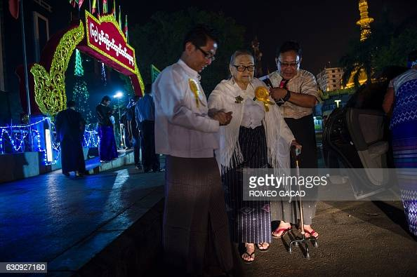 Myanmar independence veteran and grandmother Nyin Nay is assisted by relatives after participating in a dawn flagraising ceremony at Yangon's central...