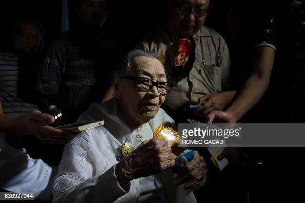 Myanmar independence veteran and grandmother Nyin Nay is interviewed by journalists after participating in a dawn flagraising ceremony at Yangon's...