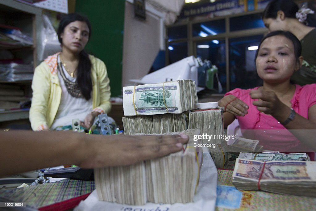 Myanmar kyat banknotes sit in bundles after being counted at a store in Yangon, Myanmar, on Tuesday, Jan. 22, 2013. Myanmar cleared about $1 billion in overdue debt with the Asian Development Bank and World Bank using a bridge loan from Japan, opening the door for increased lending as the country seeks to overhaul its infrastructure. Photographer: Brent Lewin/Bloomberg via Getty Images