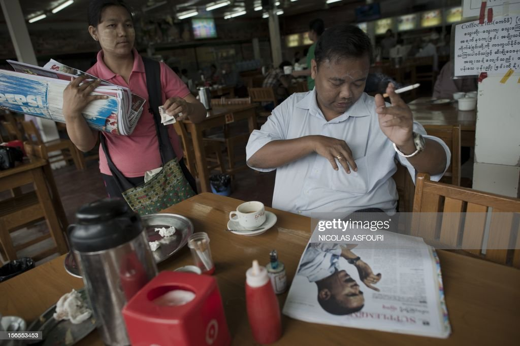 A Myanmar man buys a newspaper featuring a photograph of US president Barack Obama (bottom R) at a cafe in Yangon, on November 17, 2012. Myanmar's government has said it 'warmly welcomes' the historic visit of US President Barack Obama later this month, expressing hope his trip will bolster the nation's political reform drive. AFP PHOTO/ Nicolas ASFOURI