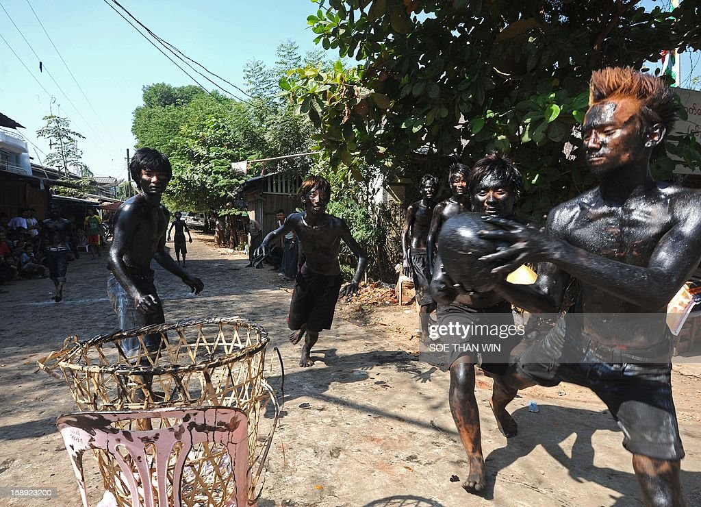 A Myanmar man (R) smeared with used car oil attempts to score a goal by placing an oiled coconut into a basket as he takes part in ball game to celebrate the 65th anniversary of Myanmar's independence, in Yangon on January 4, 2013. Myanmar, formerly known as Burma, gained independence from Britain on January 4, 1948. AFP PHOTO / Soe Than WIN