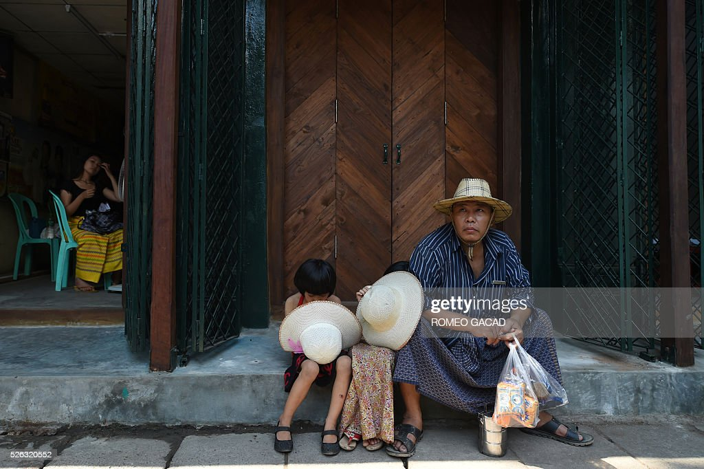 A Myanmar man wearing the traditional longyi outfit sits with two children keeping their hats under a shade in Yangon on April 30, 2016. The Meteorology and Hydrology Department has predicted that Myanmar will experience drought and record high temperatures following the effects of El Ni��o in March, April and May. / AFP / ROMEO
