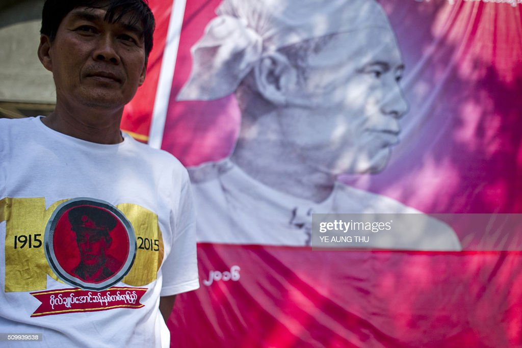 A Myanmar man wears a t-shirt and stands next to a banner showing portraits of independence hero Aung San, responsible for the country's independence from British rule and father of Aung San Suu Kyi, during a ceremony to mark his 101th birth anniversary at the National League for Democracy's (NLD) headquarters in Yangon on February 13, 2016. Known affectionately as 'Bogyoke', or General, Aung San is adored in Myanmar and credited with unshackling the country from colonial rule and embracing its ethnic minorities in a vision of unity that unravelled catastrophically in the military-dominated decades that followed his 1947 assassination. AFP PHOTO / YE AUNG THU / AFP / Ye Aung Thu