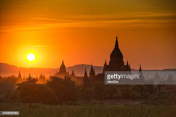 Myanmar, Mandalay, Bagan, Stupas of Buddhist temples silhouetted against morning sky