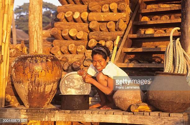 Myanmar, Mandalay, girl smiling doing washing, portrait