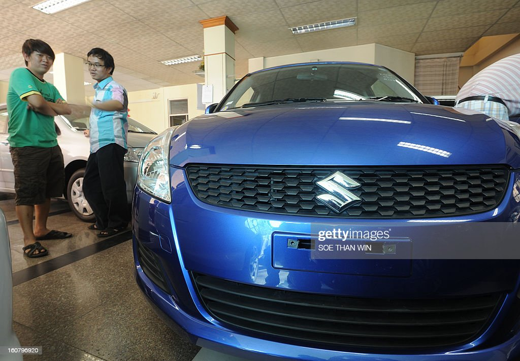 Myanmar men look at a Suzuki car at a show room in Yangon on February 6, 2013. Japanese automaker Suzuki said on February 6 it will resume production in Myanmar, the latest in a push by Asia's second-biggest economy to tap the once-isolated state. AFP PHOTO/ Soe Than WIN