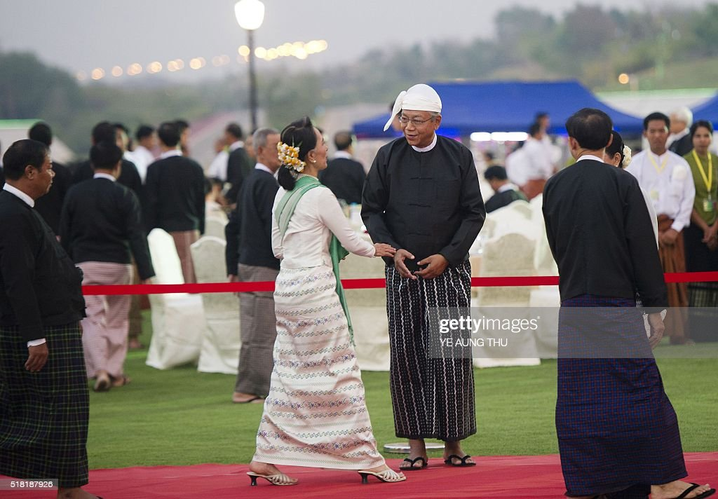 Myanmar National League for Democracy leader Aung San Suu Kyi is welcomed by new Myanmar President Htin Kyaw during a dinner reception following a...