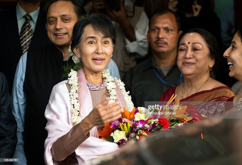Myanmar opposition leader and National League for Democracy Chairperson Aung San Suu Kyi (C) gestures while welcomed by Principal of Lady Sri Ram College Meenakshi Gopinath (R) during her visit to the college in New Delhi on November 16, 2012. Suu Kyi is in India for a seven day visit. AFP PHOTO/ Prakash SINGH