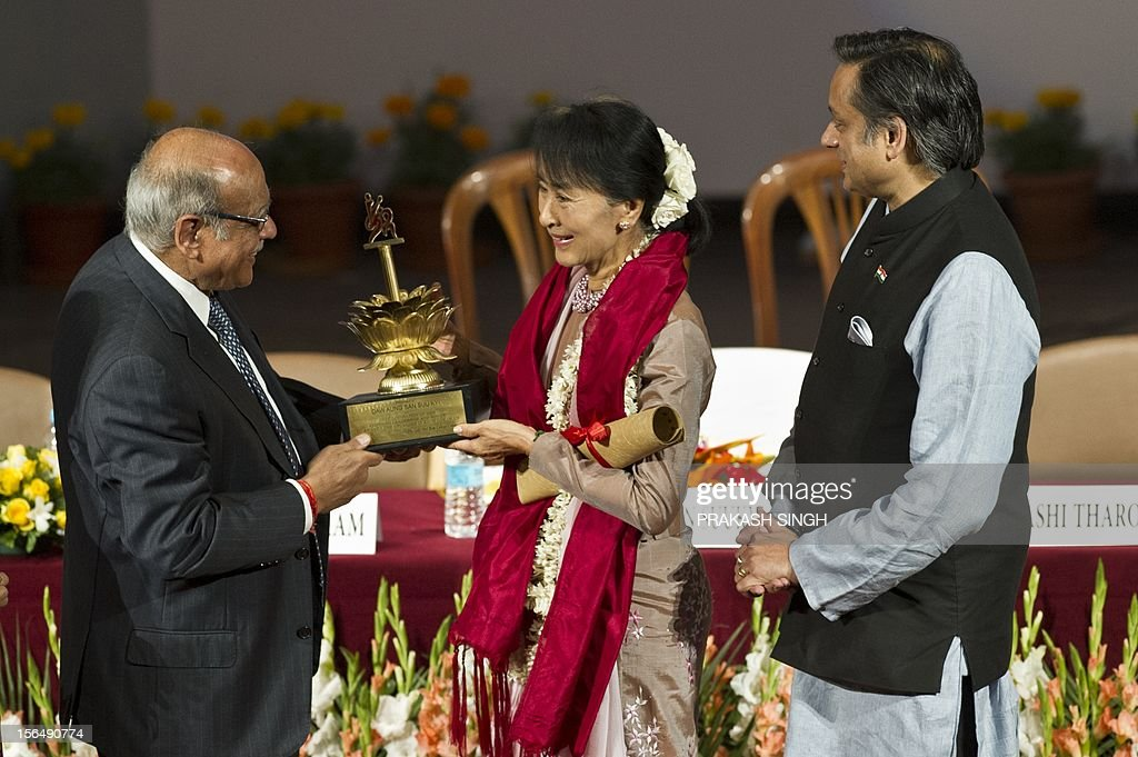 Myanmar opposition leader and National League for Democracy Chairperson Aung San Suu Kyi (C) receives a souvenir from Chairman of Lady Sri Ram college Arun Bharat Ram (L) while Indian Human Resource Development Minister Shashi Tharoor (R) looks on during her visit to Lady Sri Ram College in New Delhi on November 16, 2012. Suu Kyi is in India for a seven day visit. AFP PHOTO/ Prakash SINGH