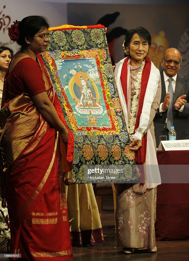 Myanmar opposition leader and National League for Democracy Chairperson Aung San Suu Kyi with a thangka painting presented to her as a gift during her visit to Lady Sri Ram College her alma mater on November 16, 2012 in New Delhi, India.