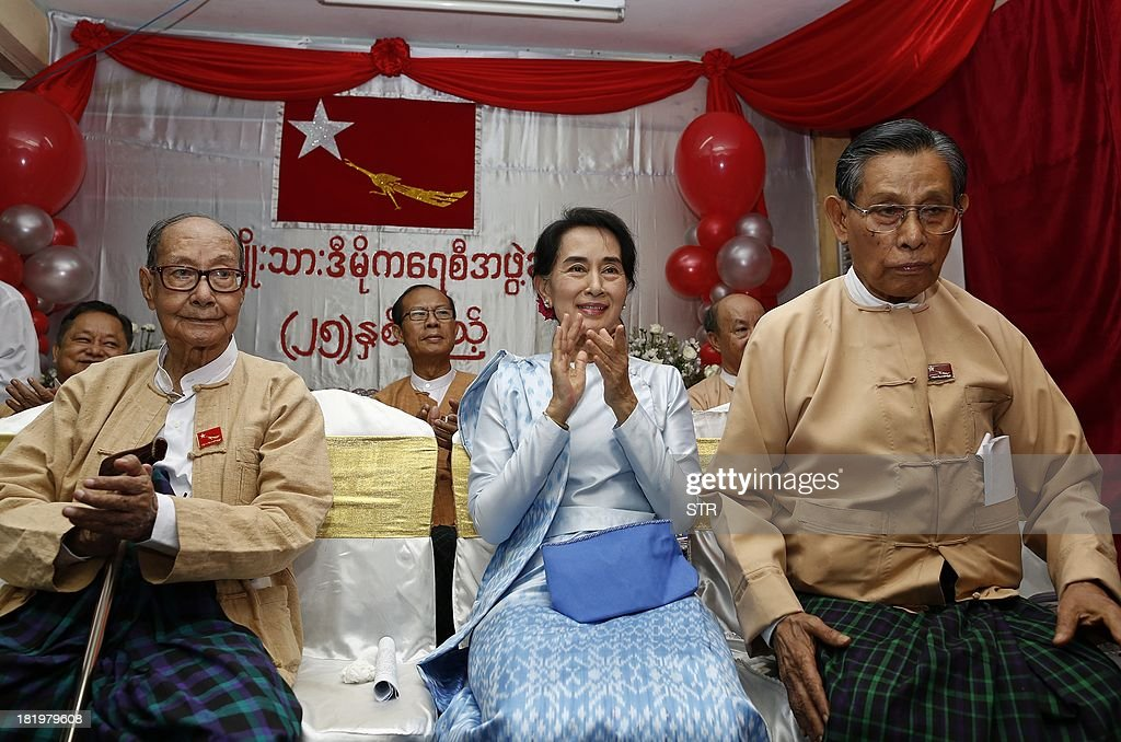 Myanmar opposition leader Aung San Suu Kyi (C) applauds during a ceremony at the National League for Democracy (NLD) headquarters in Yangon on September 27, 2013. Suu Kyi addressed members of the NLD on the occasion of the 25th anniversary of the founding of her party.