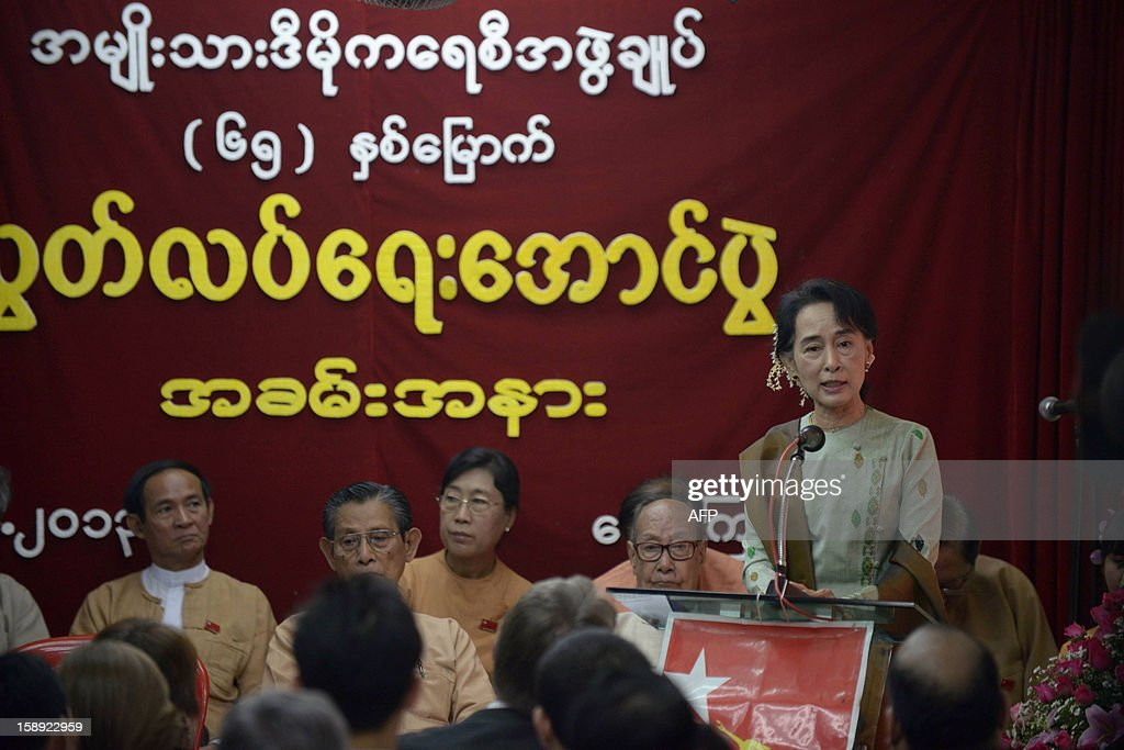 Myanmar opposition leader <a gi-track='captionPersonalityLinkClicked' href=/galleries/search?phrase=Aung+San+Suu+Kyi&family=editorial&specificpeople=214208 ng-click='$event.stopPropagation()'>Aung San Suu Kyi</a> (R, standing) delivers a speech to mark the 65th anniversary of Myanmar's independence at the head office of the National League for Democracy (NLD) party in Yangon on January 4, 2013. Myanmar, formerly known as Burma, gained independence from Britain on January 4, 1948.