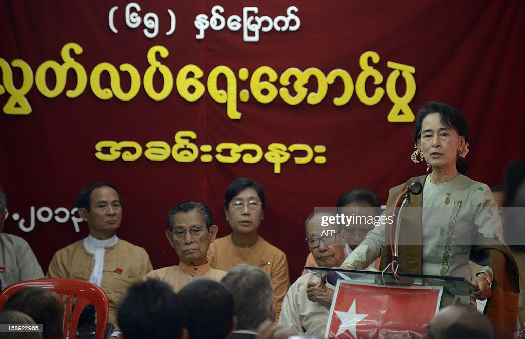 Myanmar opposition leader Aung San Suu Kyi (R) delivers a speech to mark the 65th anniversary of Myanmar's independence at the head office of the National League for Democracy (NLD) party in Yangon on January 4, 2013. Myanmar, formerly known as Burma, gained independence from Britain on January 4, 1948.