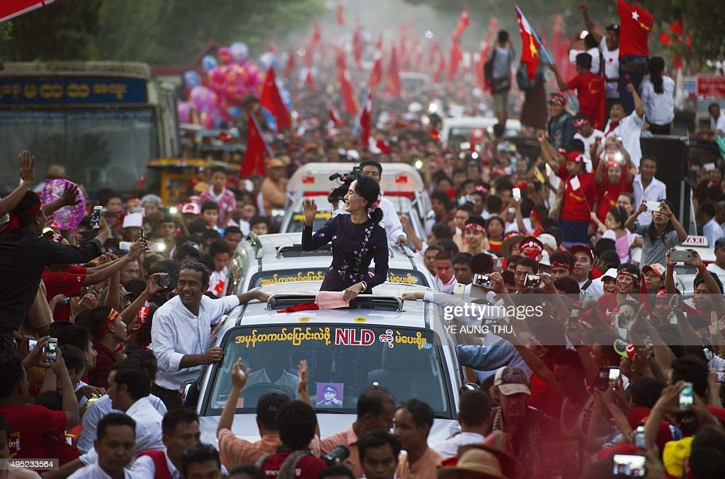 Myanmar opposition leader <a gi-track='captionPersonalityLinkClicked' href=/galleries/search?phrase=Aung+San+Suu+Kyi&family=editorial&specificpeople=214208 ng-click='$event.stopPropagation()'>Aung San Suu Kyi</a> gestures towards supporters as she travels in a motorcade ahead of a campaign rally for the National League for Democracy in Yangon on November 1, 2015. Myanmar heads to the polls on November 8 in what observers and voters hope will be the fairest election in decades as the nation slowly shakes off years of brutal and isolating junta rule. AFP PHOTO / Ye Aung THU