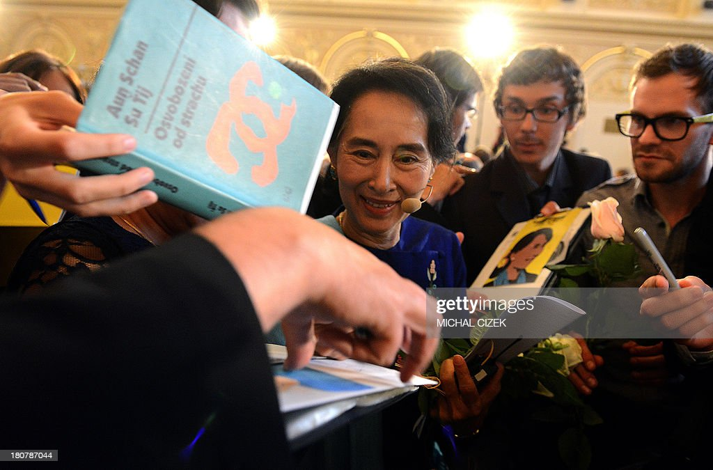 Myanmar opposition leader Aung San Suu Kyi (C) gives autographs during the 17th Forum 2000 Conference focusing on Societies and transition, September 16, 2013, in Prague. Myanmar opposition leader Aung San Suu Kyi has risked prompting Chinese anger after it was confirmed she had a private meeting with the Dalai Lama on the sidelines of a Prague rights conference, its spokesman said Monday.