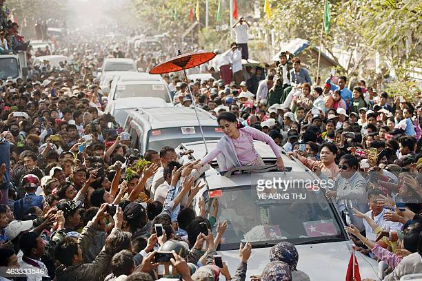 Myanmar opposition leader Aung San Suu Kyi greets supporters as she leaves celebrations to mark the 100th birthday of the country's independence hero...