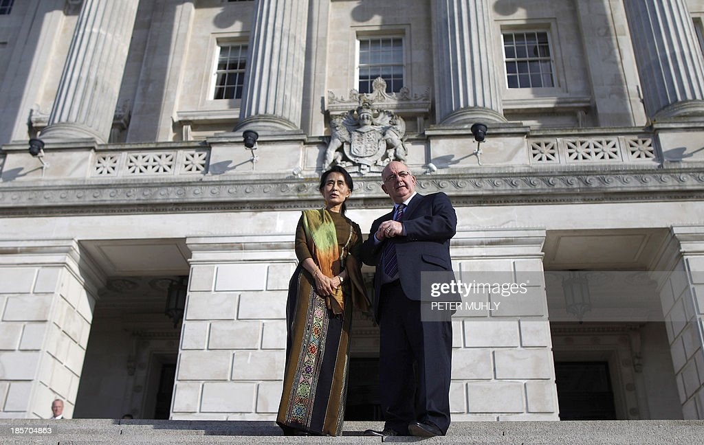 Myanmar opposition leader Aung San Suu Kyi (L) is greeted by the Speaker of the Assembly William Hay (R) as she arrives at Stormont Parliament building in Belfast, Northern Ireland, on October 24, 2013.
