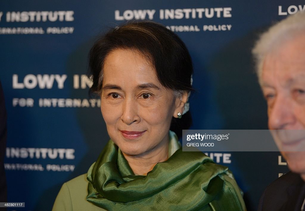 Myanmar opposition leader Aung San Suu Kyi (C) poses for a photograph with Lowe institute chairman Frank Lowe (R) after arriving for an event at the Lowy institute for international policy in Sydney on November 28, 2013. Suu Kyi was involved in an interview style conversation at the institute as part of her five-day trip to Australia, where she will visit Sydney, Canberra and Melbourne. AFP PHOTO / Greg WOOD