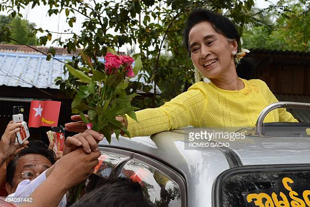 Myanmar opposition leader Aung San Suu Kyi receives roses from a supporter during a campaign rally for the National League for Democracy in Kawhmu on...