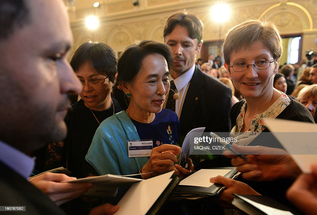 Myanmar opposition leader Aung San Suu Kyi (C) signs autographs during the 17th Forum 2000 Conference focusing on Societies and transition, September 16, 2013, in Prague. Myanmar opposition leader Aung San Suu Kyi has risked prompting Chinese anger after it was confirmed she had a private meeting with the Dalai Lama on the sidelines of a Prague rights conference, its spokesman said Monday.