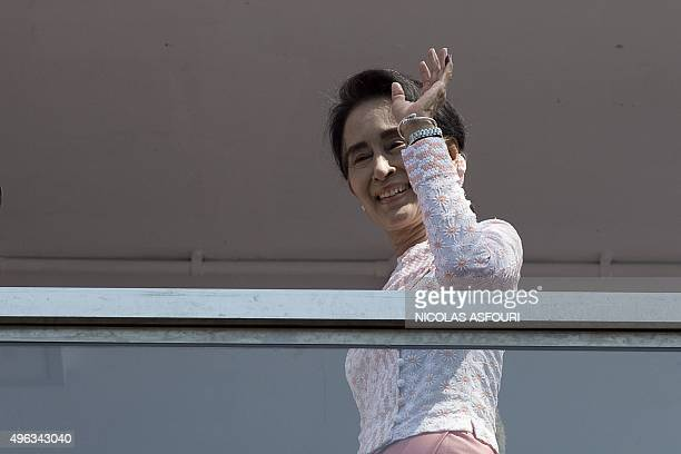 Myanmar opposition leader Aung San Suu Kyi waves to a small crowd and the media after delivering a speech from the balcony of the National League of...