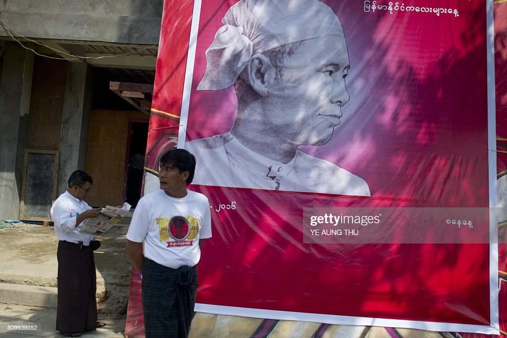 Myanmar people stand next to a banner showing a portrait of independence hero Aung San, responsible for the country's independence from British rule and father of Aung San Suu Kyi, during a ceremony to mark his 101th birth anniversary at the National League for Democracy's (NLD) headquarters in Yangon on February 13, 2016. Known affectionately as 'Bogyoke', or General, Aung San is adored in Myanmar and credited with unshackling the country from colonial rule and embracing its ethnic minorities in a vision of unity that unravelled catastrophically in the military-dominated decades that followed his 1947 assassination. AFP PHOTO / YE AUNG THU / AFP / Ye Aung Thu