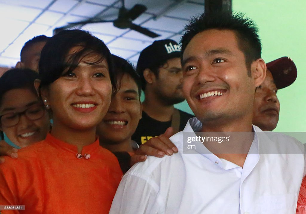 Myanmar poet Maung Saungkha (R) 24, smiles with his girlfriend Shar Yamone (L) in Yangon court on May 24, 2016 after serving a jail sentence for defamation for publishing a poem on Facebook about having a tattoo of the former president on his penis. Maung Saungkha was arrested in November after he shared the short poem. He was convicted of online defamation charges under Myanmar's telecommunications law and sentenced to six months in prison court and sentenced to six months in prison -- time he had already served. / AFP / STR