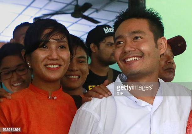 Myanmar poet Maung Saungkha 24 smiles with his girlfriend Shar Yamone in Yangon court on May 24 2016 after serving a jail sentence for defamation for...