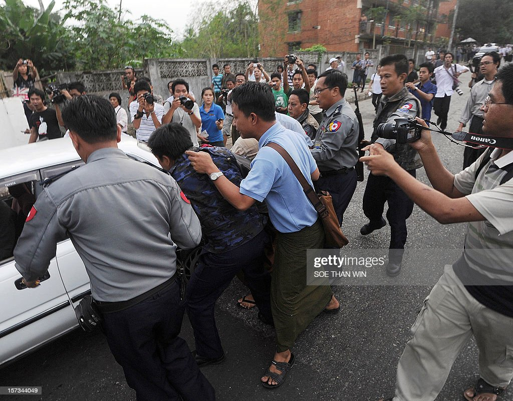 Myanmar police (L and R) arrest a protester (C) and put him into a car during a protest in Yangon on December 2, 2012. At least two people have been arrested at a rally in Yangon held to condemn a violent police crackdown on protesters at a Chinese-backed copper mine, an activist and an AFP reporter said. AFP PHOTO / Soe Than WIN
