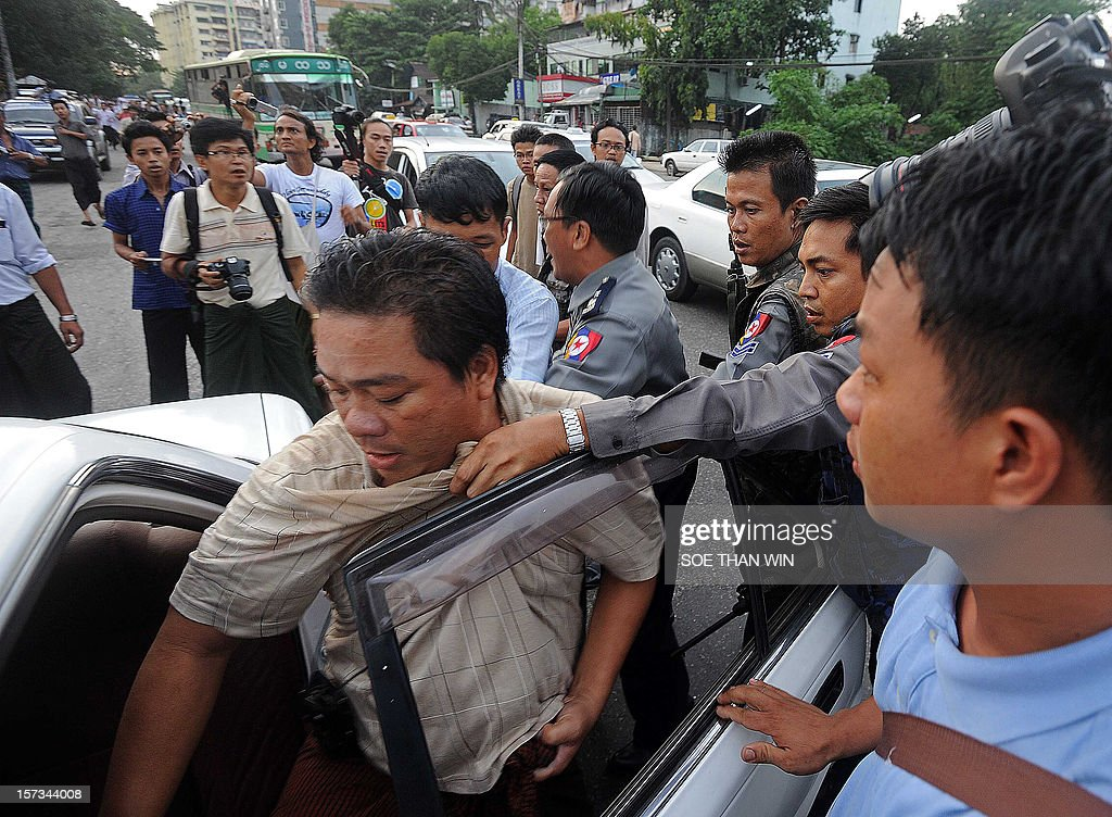 Myanmar police (back R) arrest protester Aung Soe (L) and put him into a car during a protest in Yangon on December 2, 2012. At least two people have been arrested at a rally in Yangon held to condemn a violent police crackdown on protesters at a Chinese-backed copper mine, an activist and an AFP reporter said. AFP PHOTO / Soe Than WIN