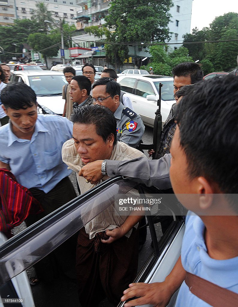 Myanmar police (back R) arrest protester Aung Soe (C) and put him into a car during a protest in Yangon on December 2, 2012. At least two people have been arrested at a rally in Yangon held to condemn a violent police crackdown on protesters at a Chinese-backed copper mine, an activist and an AFP reporter said. AFP PHOTO / Soe Than WIN