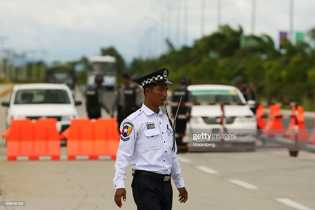 A Myanmar Police Force officer directs traffic at the entrance to the Myanmar International Convention Center ahead of the World Economic Forum on East Asia in Naypyidaw, Myanmar, on Wednesday, June 5, 2013. Myanmar hosts the three-day World Economic Forum on East Asia starting today, with heads of state and executives from companies including General Electric Co., Coca-Cola Co. and WPP Plc attending. Photographer: Dario Pignatelli/Bloomberg via Getty Images