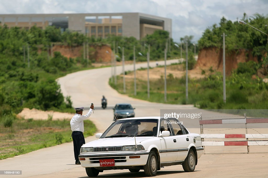 A Myanmar Police Force officer directs vehicles arriving at the Myanmar International Convention Center ahead of the World Economic Forum on East Asia in Naypyidaw, Myanmar, on Wednesday, June 5, 2013. Myanmar hosts the three-day World Economic Forum on East Asia starting today, with heads of state and executives from companies including General Electric Co., Coca-Cola Co. and WPP Plc attending. Photographer: Dario Pignatelli/Bloomberg via Getty Images