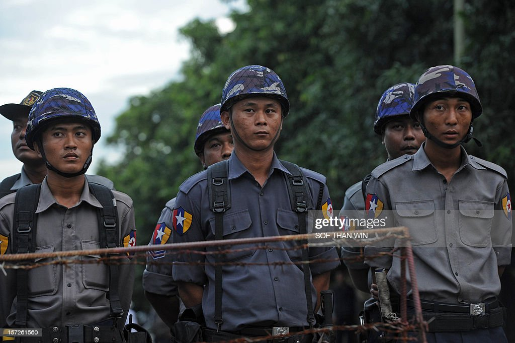Myanmar police officers stand guard in front of the Chinese embassy as people attend a protest (not pictured) nearby in Yangon on December 1, 2012. Police apologised for injuring scores of monks in a crackdown on a protest at a Chinese-backed copper mine in northern Myanmar, an AFP reporter said December 1, but tensions over the pre-dawn raid remained high. AFP PHOTO/ Soe Than WIN.