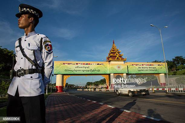 Myanmar policeman wearing his dress uniform stands guard by the ASEAN summit welcome sign on November 11 2014 in Naypyidaw Myanmar Myanmar's capitol...