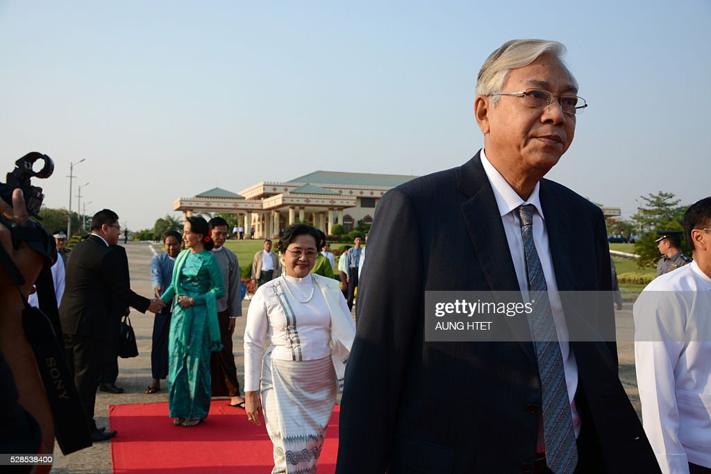 Myanmar President Htin Kyaw (R) followed by First Lady Su Su Lwin (C, in white dress) and State Counsellor and Foreign Minister Aung San Suu Kyi (L, in green dress) depart for an official trip to Laos from the Naypyidaw city airport on May 6, 2016. The official mission is their first foreign trip after being sworn into office on March 30. / AFP / AUNG