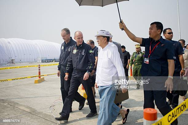 Myanmar president Thein Sein walk with Swiss pilots Andre Borschberg and Bertrand Piccard of Solar Impulse 2 at Mandalay international airport on...