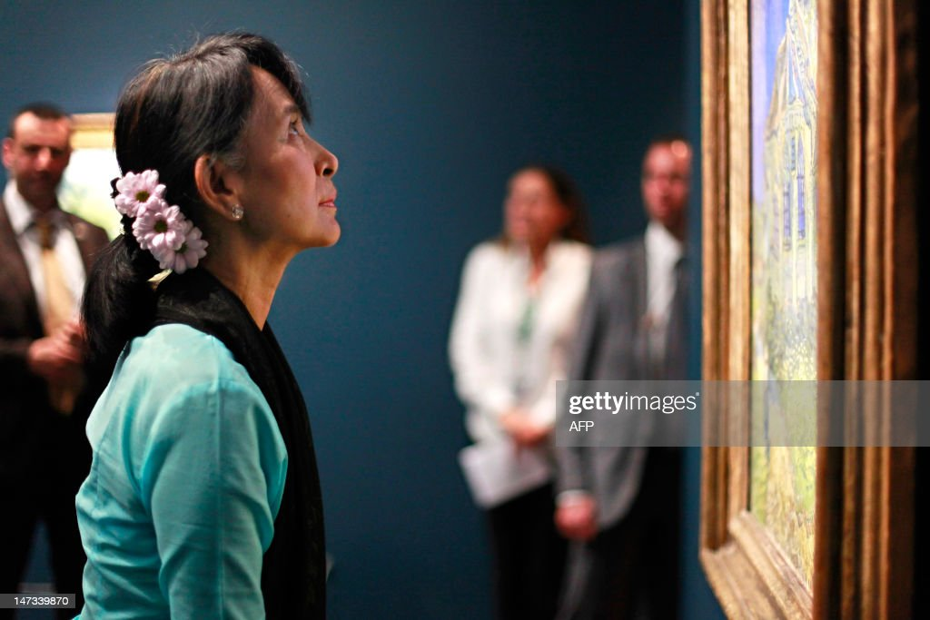 Myanmar pro-democracy leader Aung San Suu Kyi looks a Dutch Vincent Van Gogh's painting named' L'eglise d'Auvers-sur-Oise, vue du chevet' (1890), as she visits the Orsay museum, in Paris, on June 28, 2012. Myanmar's democracy champion Aung San Suu Kyi is near the end of her triumphant Europe tour in France.