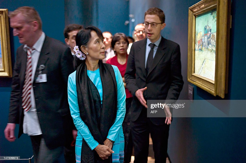 Myanmar pro-democracy leader Aung San Suu Kyi looks a Vincent Van Gogh's painting named' Les roulottes, campement de bohemiens aux environs d'Arles' (1888), as she visits the Orsay museum, in Paris, on June 28, 2012. Myanmar's democracy champion Aung San Suu Kyi is near the end of her triumphant Europe tour in France.