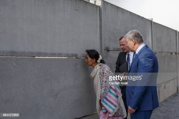 Myanmar prodemocracy leader Aung San Suu Kyi looks through the wall when Director of the Berlin Wall Memorial Axel Klausmeier and Berlin's Mayor...