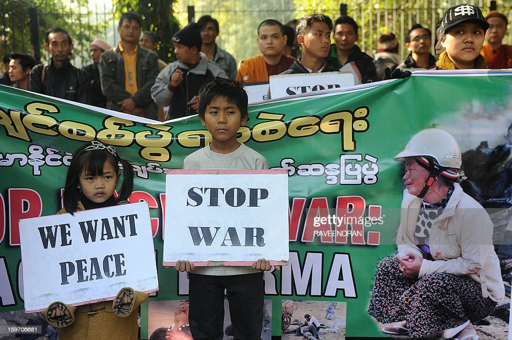 Myanmar pro-democracy movement activists, resident in India, hold placards during a protest in New Delhi on January 19, 2013 against the Myanmar government and to demand that the war in Kachin must be stopped immediately. Some 50 activists staged a demonstration as more than 100,000 civilans have been displaced from their native home, many have been killed, a third have to seek shelter in government controlled areas and two thirds are being taken care of by the Kachin Independence Organization (KIO).