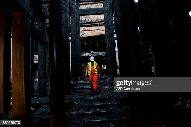A Myanmar Red Cross member works at the scene after a fire at Kandawgyi Palace hotel in Yangon on October 19 2017 One person died in a predawn blaze...