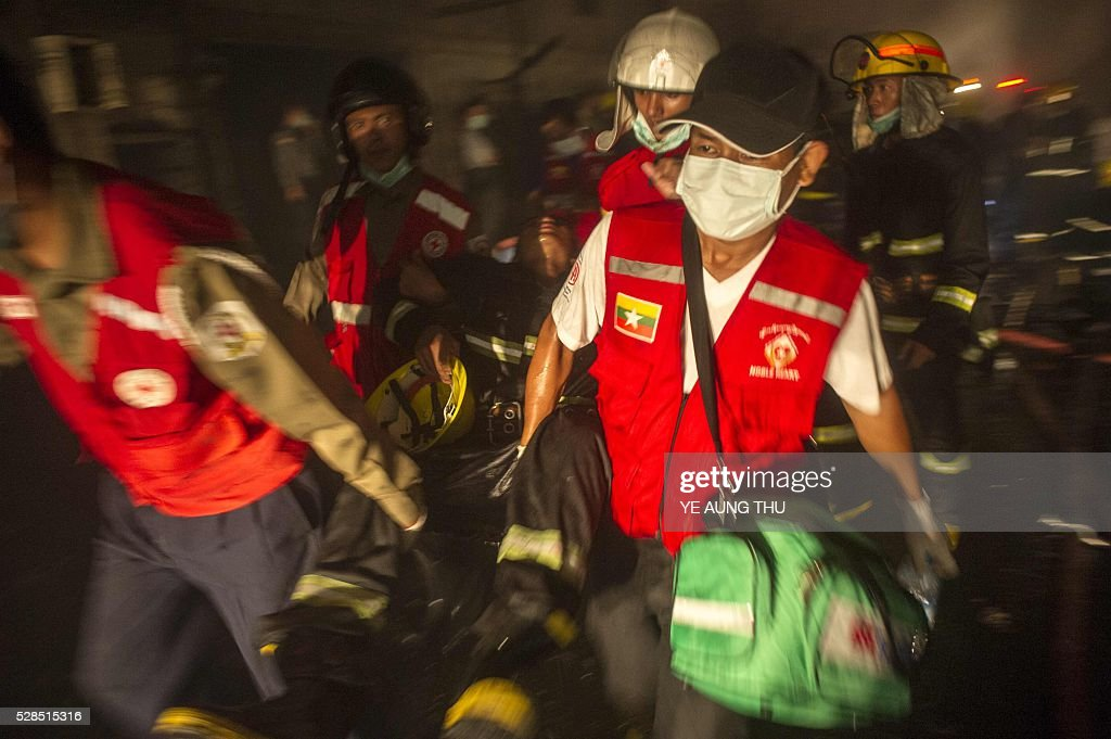 Myanmar redcross members carry a fire fighter for medical attention as he suffers from smoke inhalation after attending to a fire at the South Dagon industrial zone in Yangon, late on late May 5, 2016. / AFP / YE