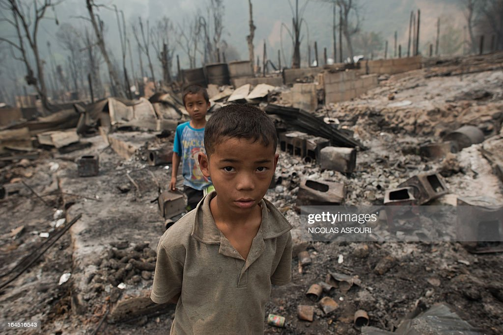 Myanmar refugee boys walk at their destroyed camp at the Mae Surin camp in Mae Hong Son province on March 24, 2013. Thai rescue workers picked through the ashes of hundreds of shelters for Myanmar refugees, after a ferocious blaze swept through a camp in northern Thailand killing 35 people. Around 100 people were injured in Friday's fire at the Mae Surin camp in Mae Hong Son province, provincial governor Narumol Paravat told AFP by telephone, giving a reduced toll from the 45 dead previously stated. AFP PHOTO/ Nicolas ASFOURI