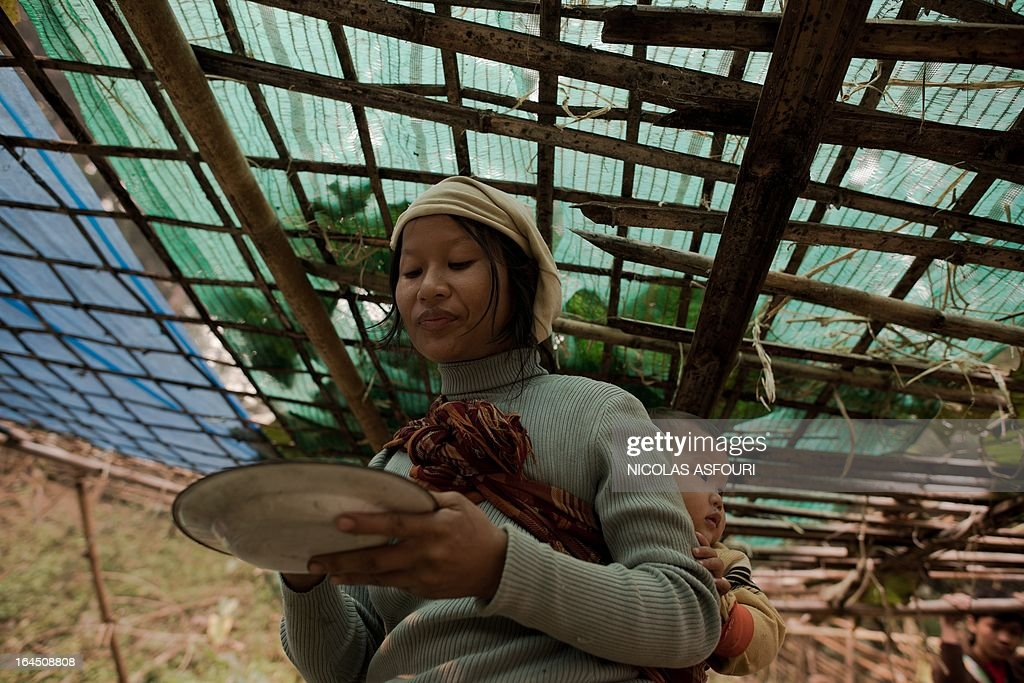 A Myanmar refugee eats food in the early morning, two days after a fire at the Mae Surin camp in Mae Hong Son province on March 24, 2013. Rescue workers on March 24 ended the search for victims of a blaze that killed 36 people tore through a Myanmar refugee camp in northern Thailand as destitute survivors scavenged for bamboo to build shelters. AFP PHOTO/ Nicolas ASFOURI