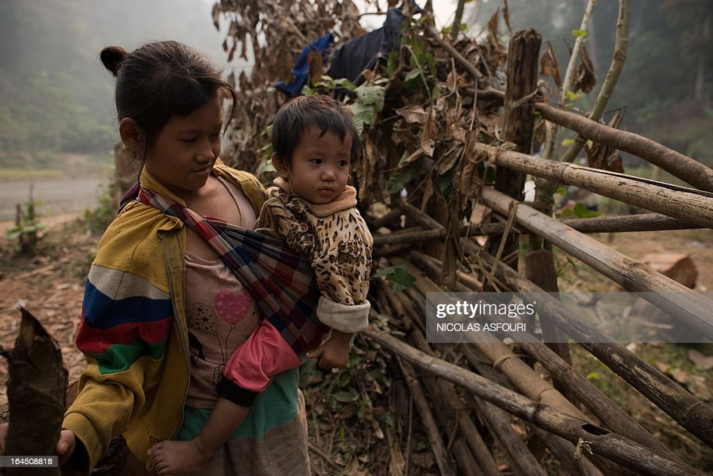 A Myanmar refugee girl carries a baby two days after a fire at the Mae Surin camp in Mae Hong Son province on March 24, 2013. Rescue workers on March 24 ended the search for victims of a blaze that killed 36 people tore through a Myanmar refugee camp in northern Thailand as destitute survivors scavenged for bamboo to build shelters. AFP PHOTO/ Nicolas ASFOURI